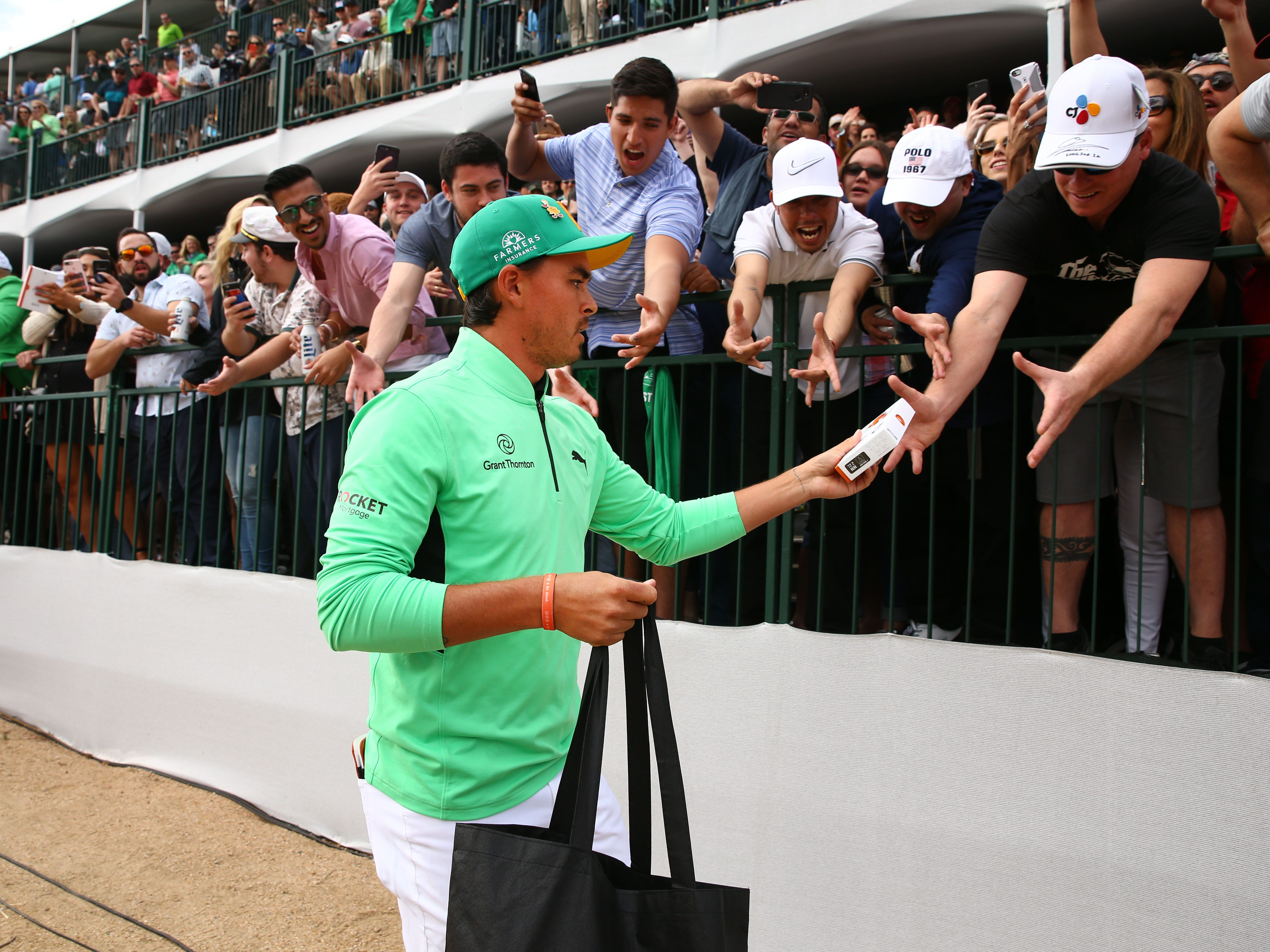 Rickie Fowler gives some gifts to the fans on the 16th hole during third round action on Feb. 2 during the Waste Management Phoenix Open at the TPC Scottsdale Stadium Course.