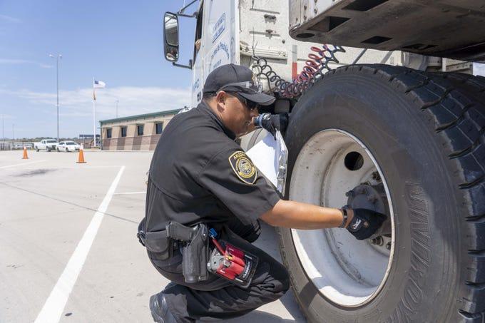 Juan Jimenez, an ADOT enforcement officer, inspects a truck of Francisco Bustamante's at ADOT Nogales facility