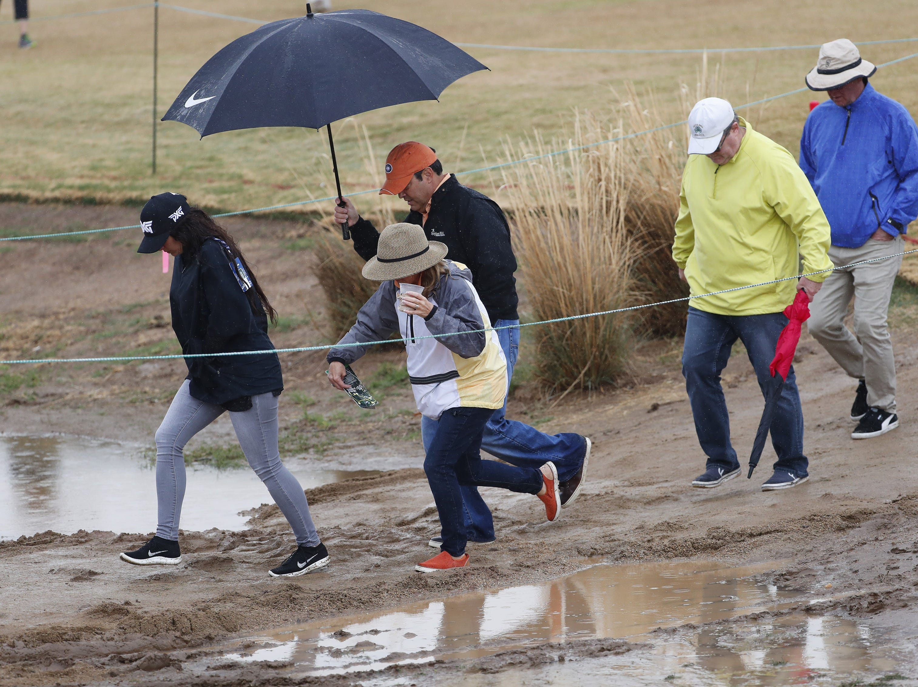 Fans walk through mud during the final round of the Waste Management Phoenix Open at the TPC Scottsdale Feb. 3, 2019.