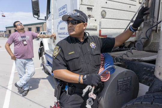 Juan Jimenez, an ADOT enforcement officer, inspects a truck of Francisco Bustamante's at the ADOT Nogales facility.