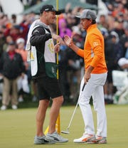 Caddie Joe Skovron congratulates Rickie Fowler after winning the Waste Management Phoenix Open at the TPC Scottsdale Feb. 3, 2019.