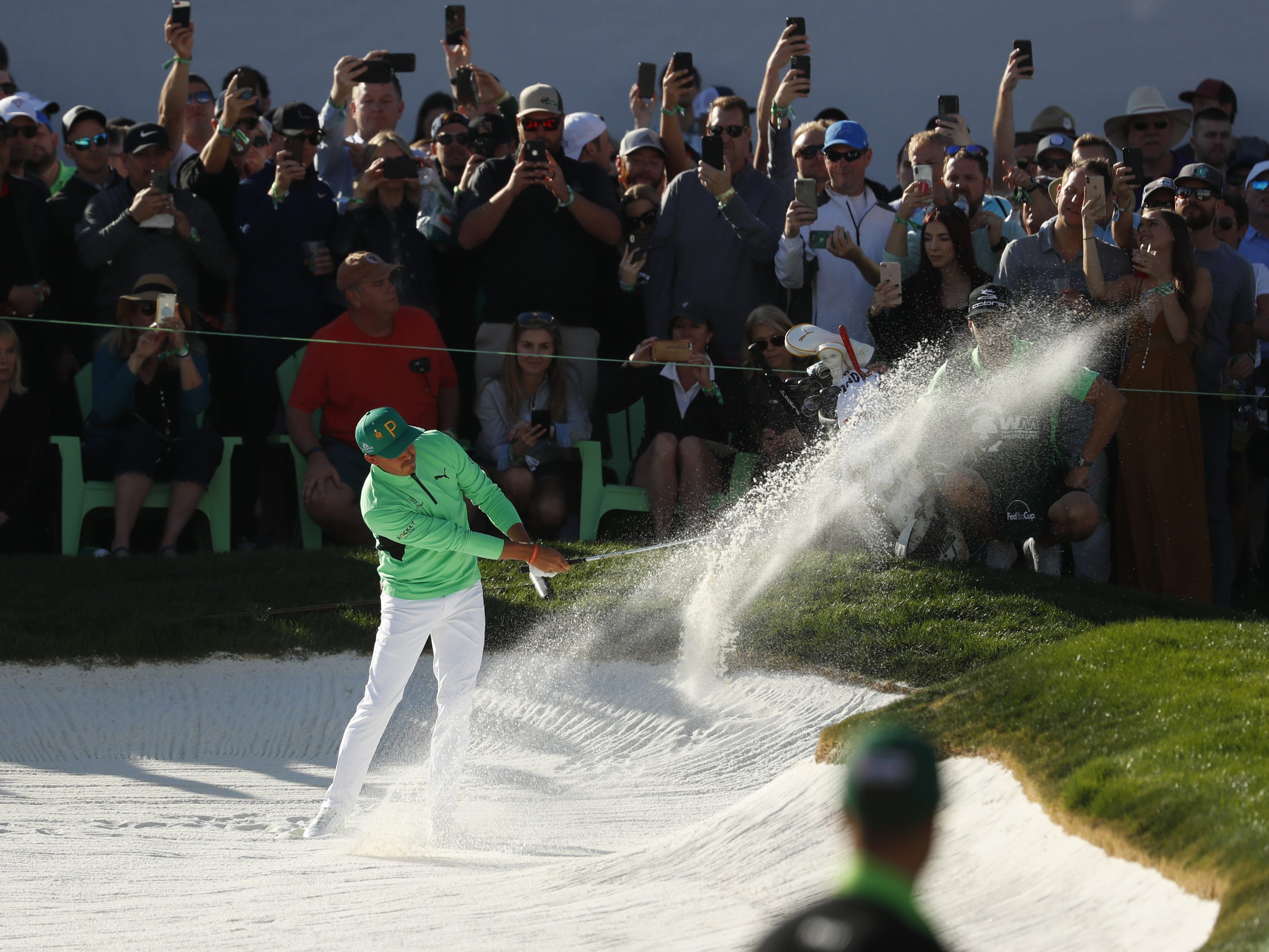 Rickie Fowler hits from a fairway bunker on the 18th hole during the third round of the Waste Management Phoenix Open at TPC Scottsdale in Scottsdale, Ariz. on February 2, 2019.