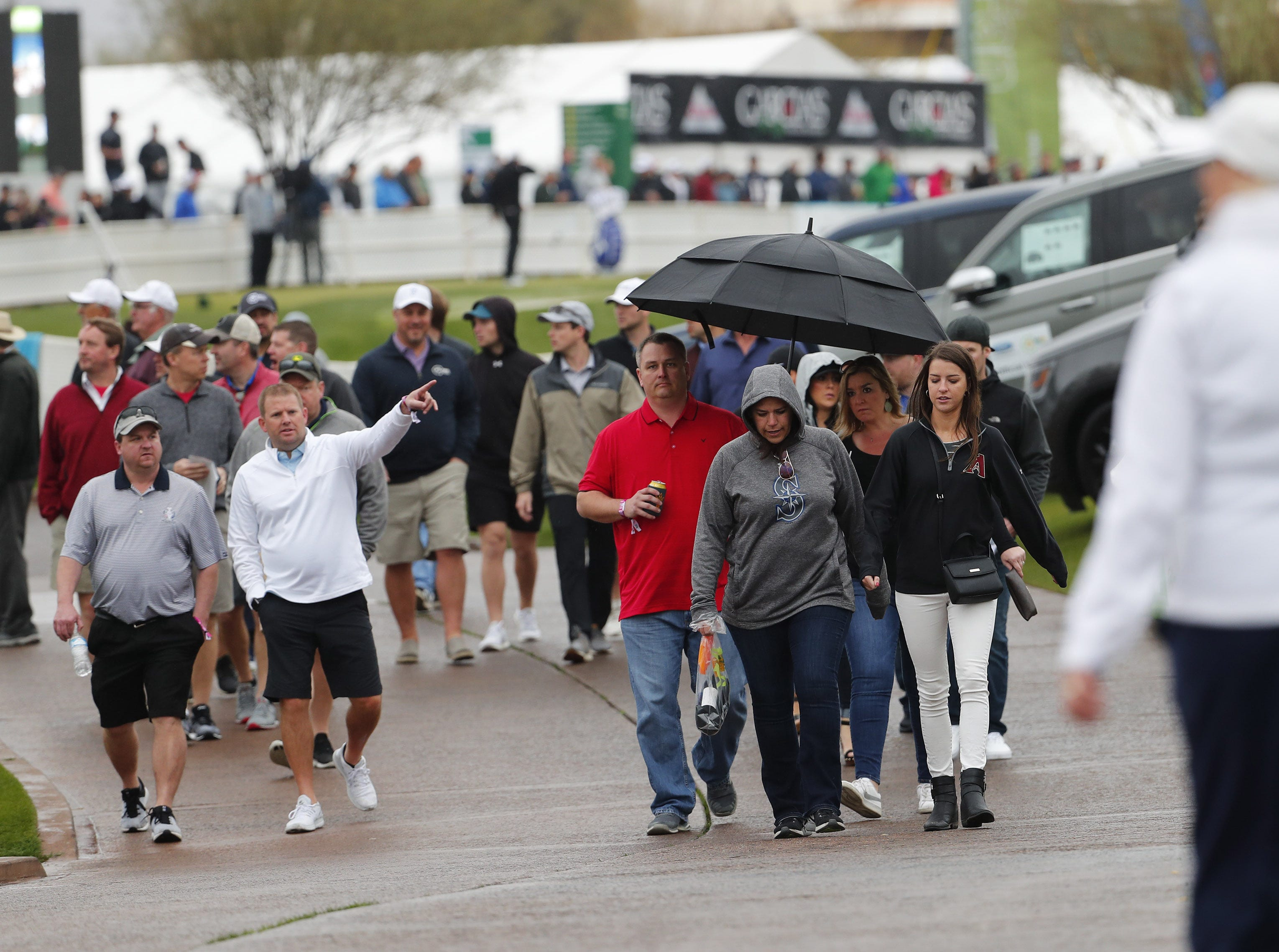 Fans try to stay dry while watching the final round of the Waste Management Phoenix Open at the TPC Scottsdale Feb. 3, 2019.