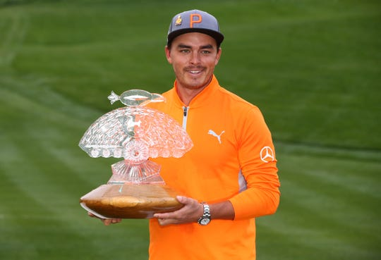 Rickie Fowler holds up the trophy after winning the 2019 Waste Management Phoenix Open at the TPC Scottsdale.