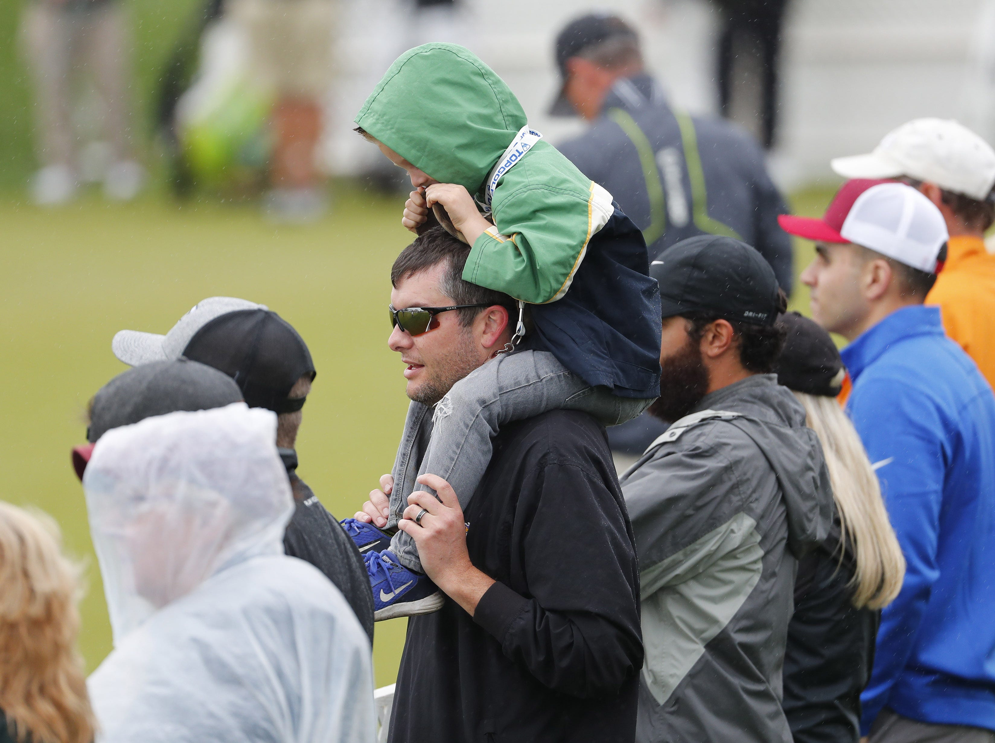 Tim Armbrust carries his son, Bennett, 4, on his shoulders while watching the final round of the Waste Management Phoenix Open at the TPC Scottsdale Feb. 3, 2019.
