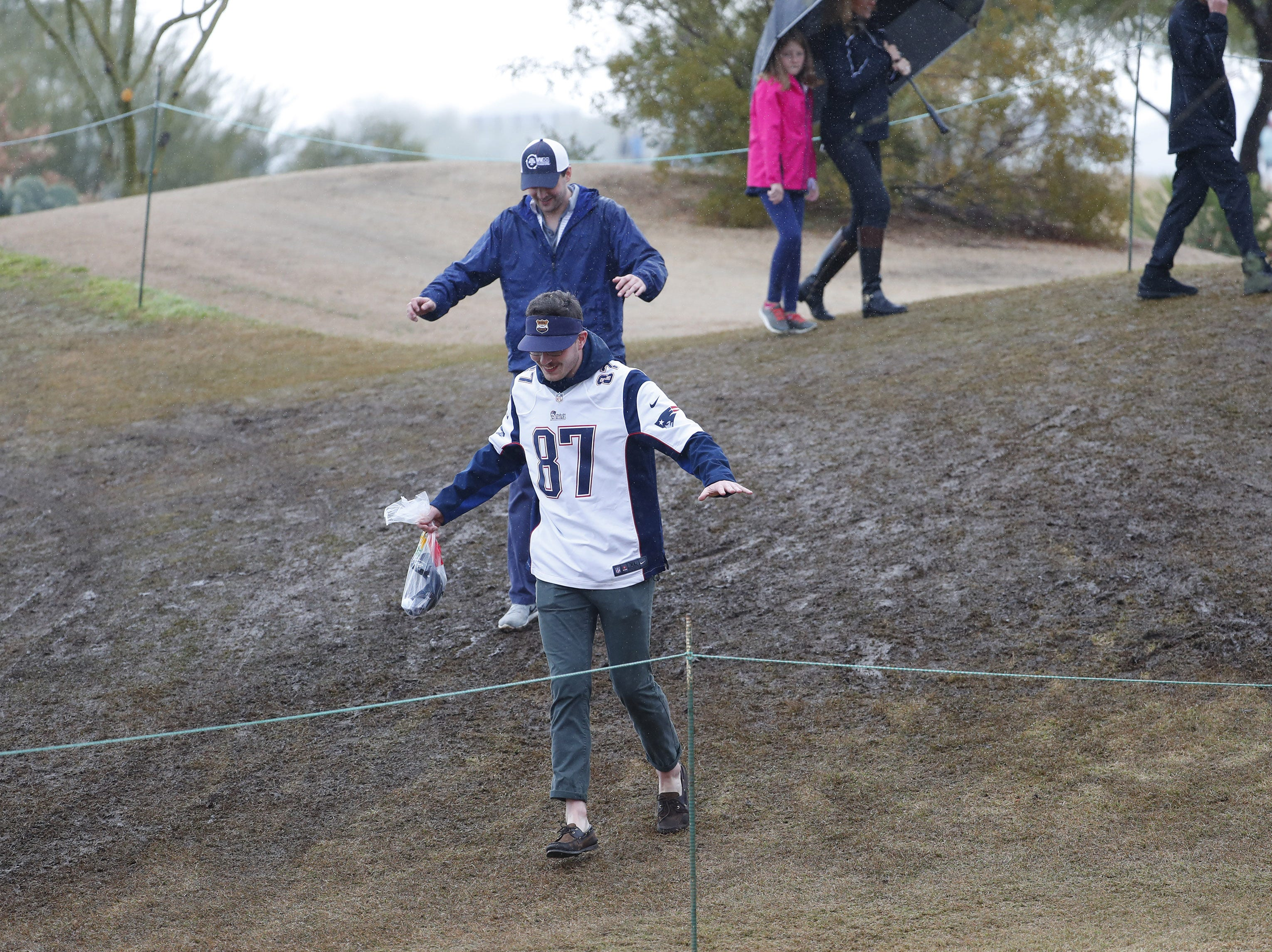 Fans make their way down a muddy hill during the final round of the Waste Management Phoenix Open at the TPC Scottsdale Feb. 3, 2019.