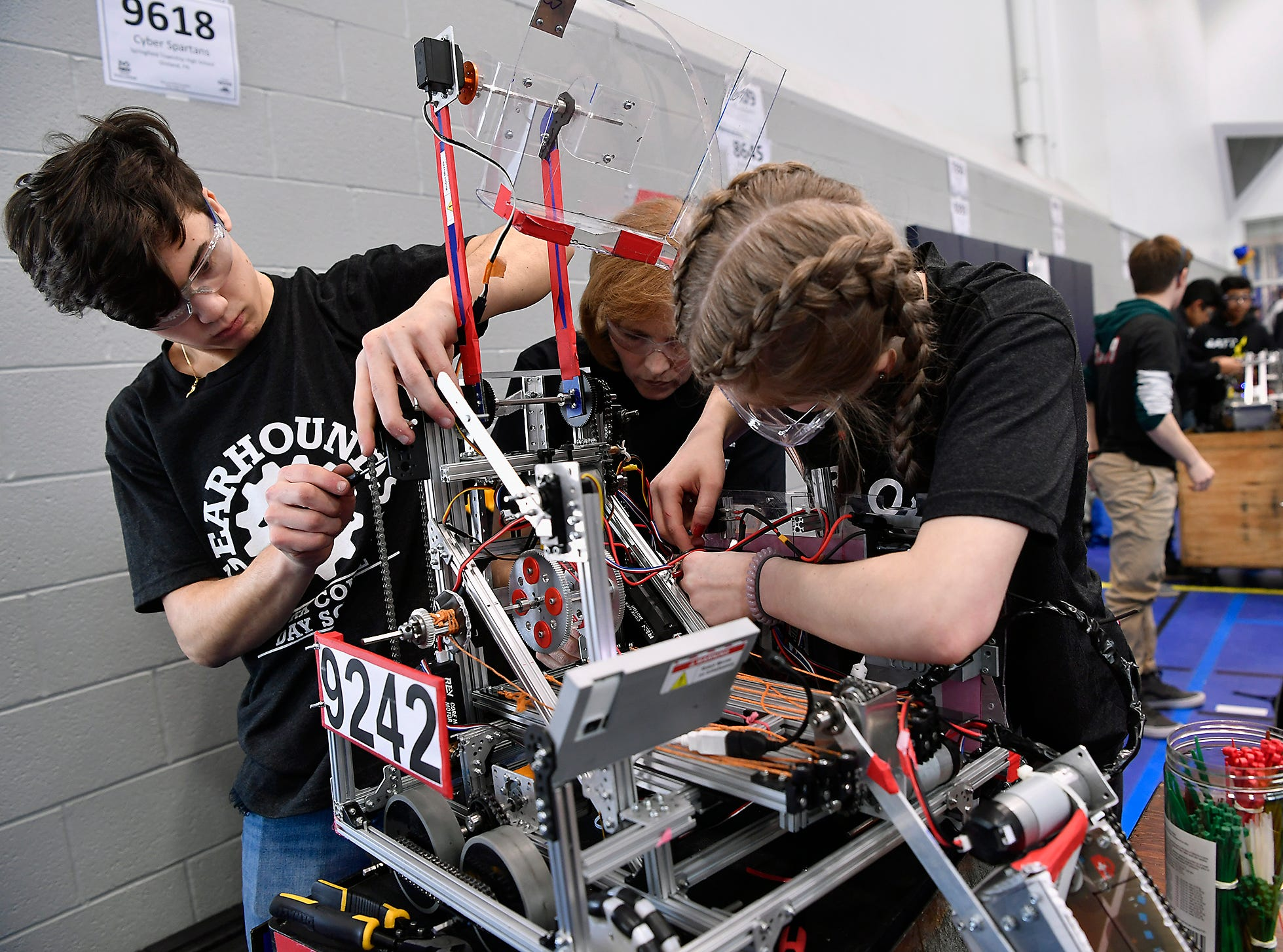 York Country Day students Christian Morino, left, and Juliet Jacob work with advisor Amy Harmon-Krtanjek to make adjustments to the GearHounds robot during the Rover Ruckus robotics tournament at Penn State York, Sunday, February 3, 2019. John A. Pavoncello photo