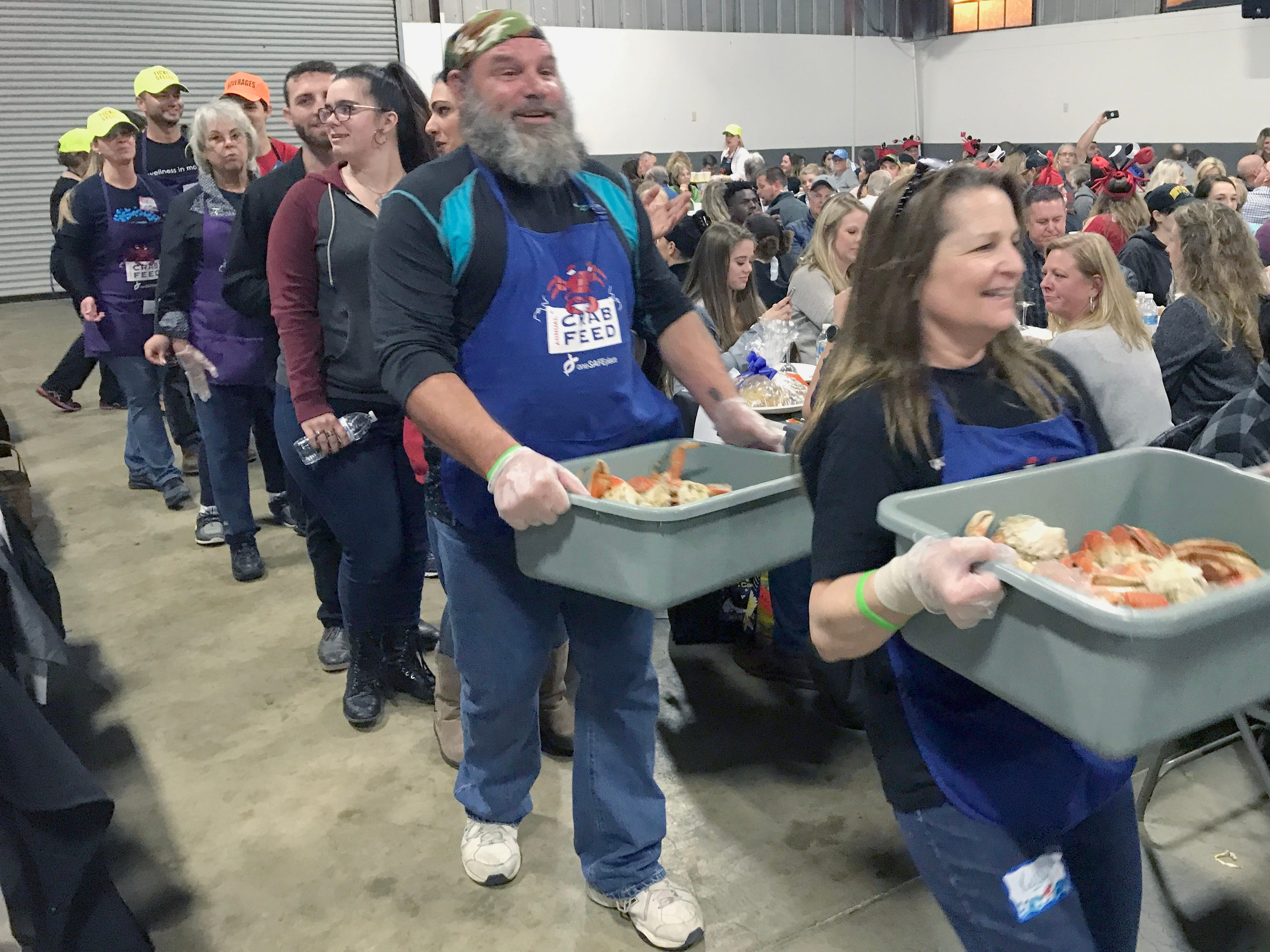 Crab servers make their grand entrance Saturday at One SAFE Place's annual crab feed.