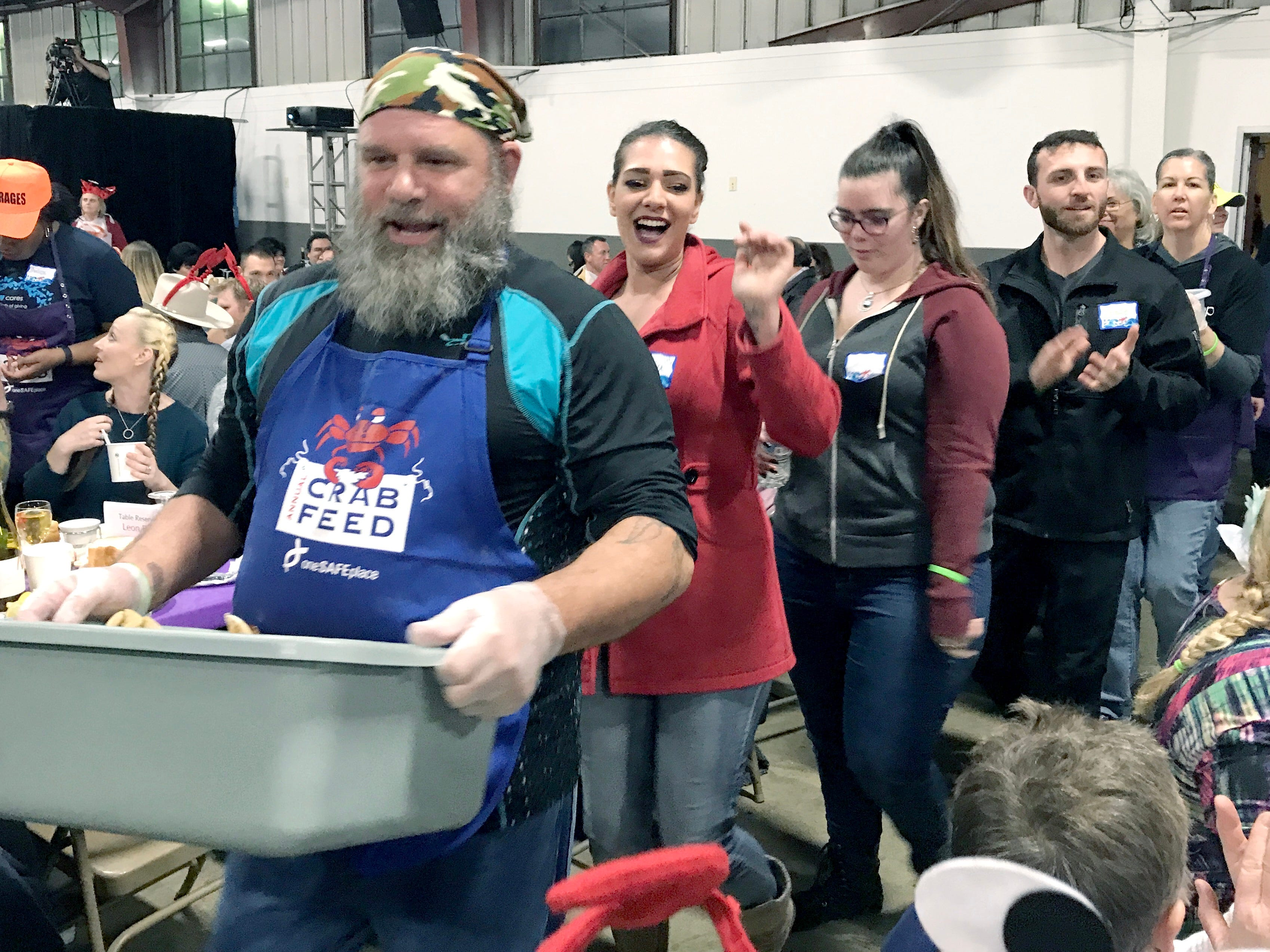 Crab servers enthusiastically enter One SAFE Place's annual crab feed Saturday, Feb. 2, 2019.