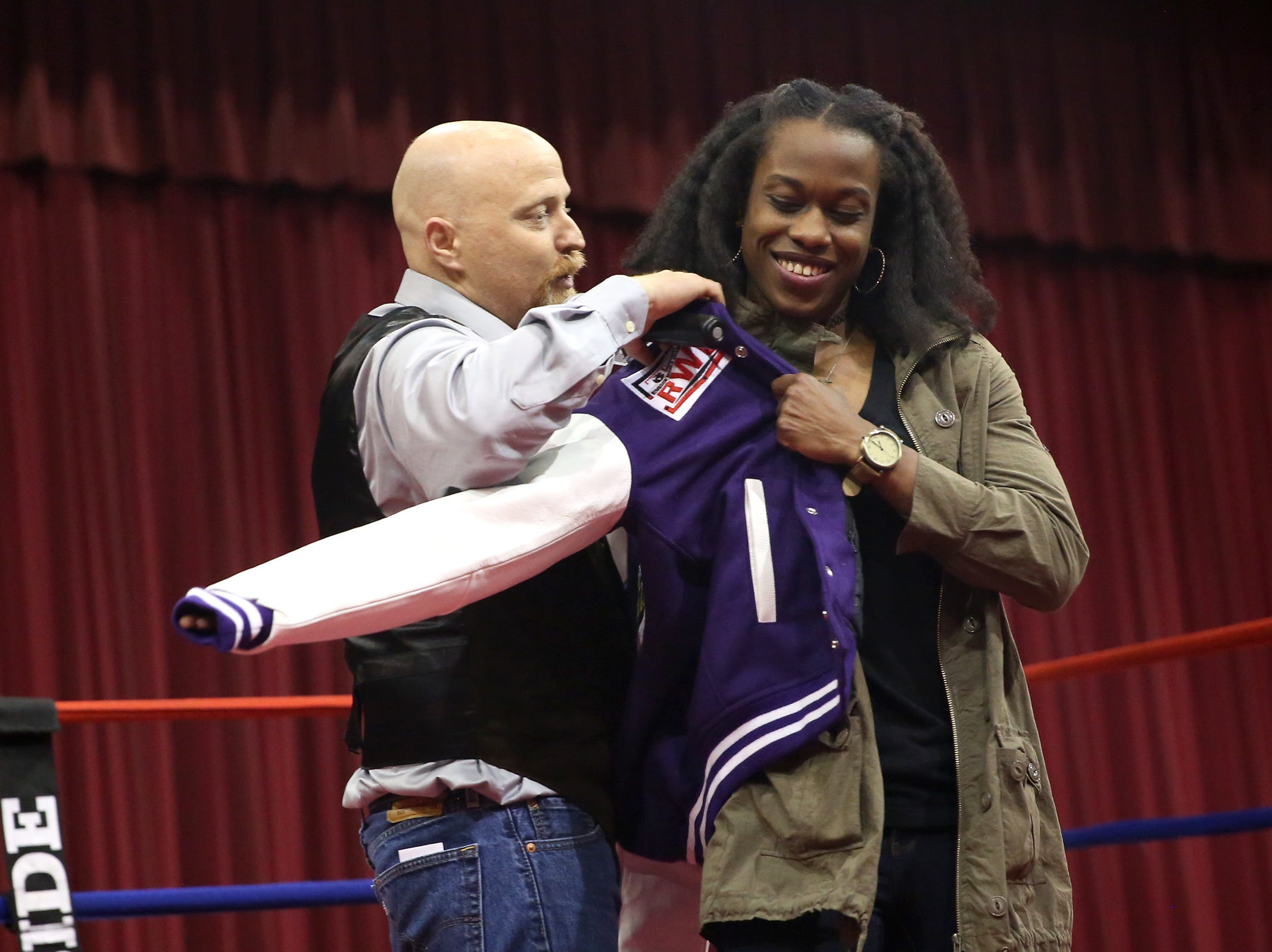 Oregon Golden Gloves state director Daniel Dunn helps Salem's Brittany Sims put on a customized championship letterman jacket at the Salem Armory on Saturday, Feb. 2, 2019.