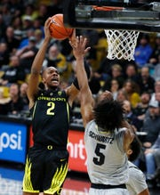Oregon forward Louis King, left, drives the lane to the rim as Colorado guard D'Shawn Schwartz defends in the first half of an NCAA college basketball game Saturday, Feb. 2, 2019, in Boulder, Colo.