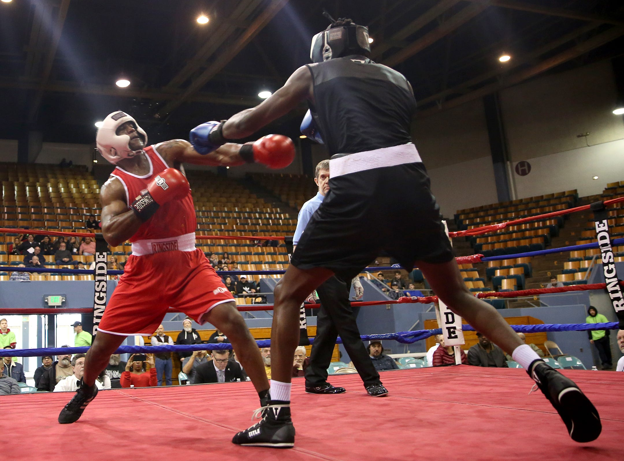 Xecareus Walker of Kent, Washington (right) takes a jab at Michad McMillan of Tigard (left) in the first bout of the Oregon Golden Gloves championship matches at the Salem Armory on Saturday, Feb. 2, 2019.