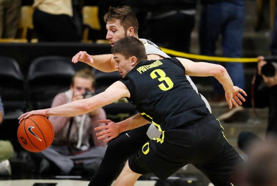 Oregon guard Payton Pritchard, front, steals a pass intended for Colorado forward Lucas Siewert in the first half of an NCAA college basketball game Saturday, Feb. 2, 2019, in Boulder, Colo.