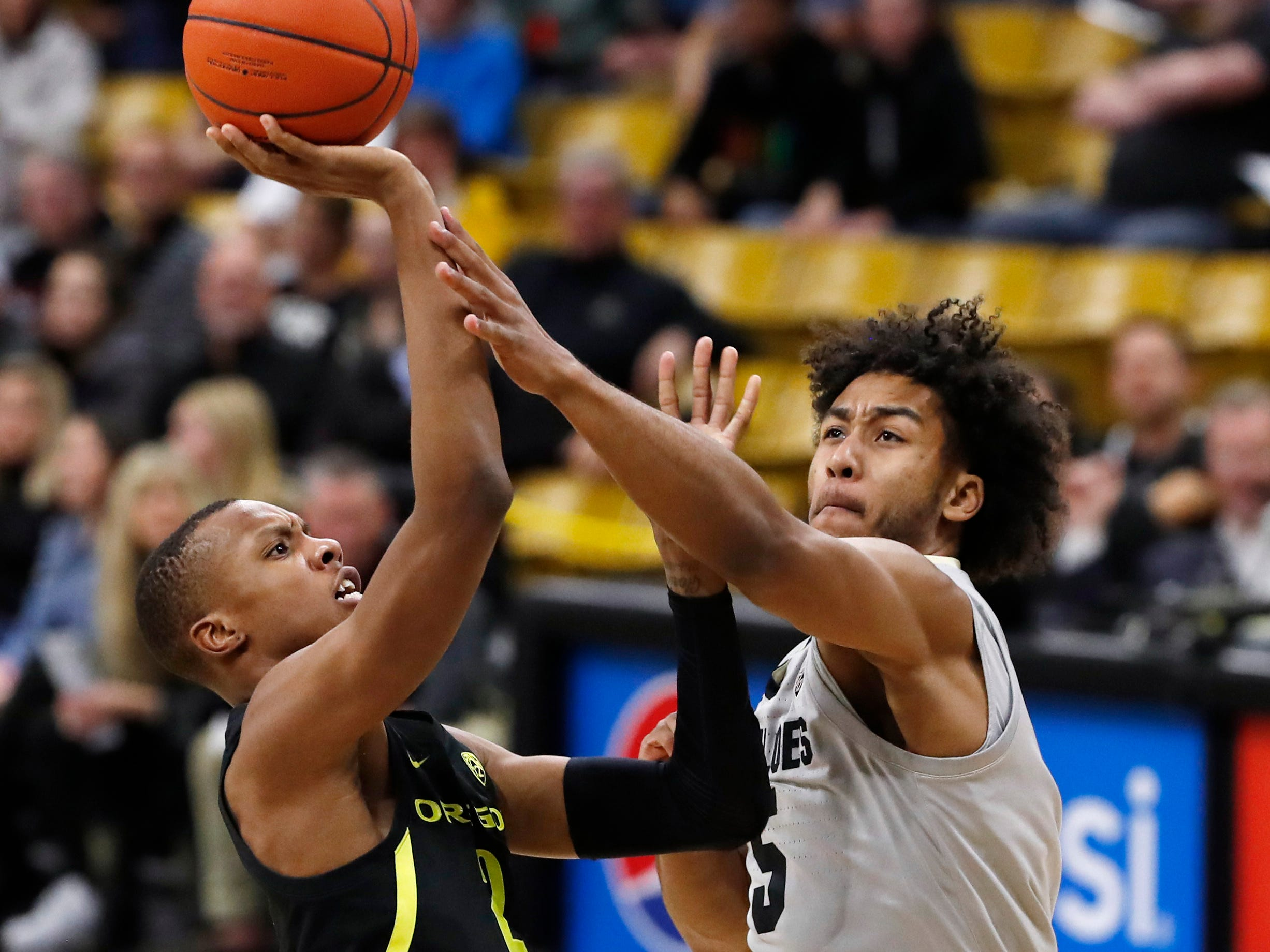 Oregon forward Louis King, left, goes up for a basket as Colorado guard D'Shawn Schwartz defends in the first half of an NCAA college basketball game Saturday, Feb. 2, 2019.