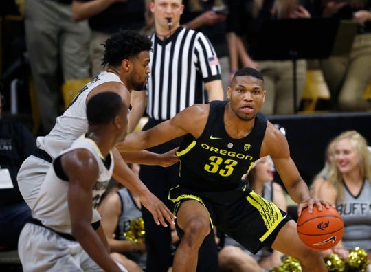 Oregon forward Francis Okoro, right, looks to pass the ball as Colorado guard McKinley Wright IV, front left, and forward Evan Battey defend during the second half of an NCAA basketball game Saturday, Feb. 2, 2019, in Boulder, Colo. Colorado won 73-51.