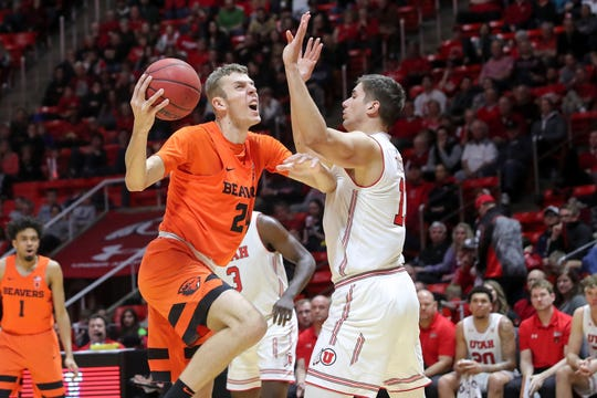 Oregon State forward Kylor Kelley (24) protects the ball from Utah forward Both Gach (11) during the first half of an NCAA college basketball game Saturday, Feb. 2, 2019, in Salt Lake City.
