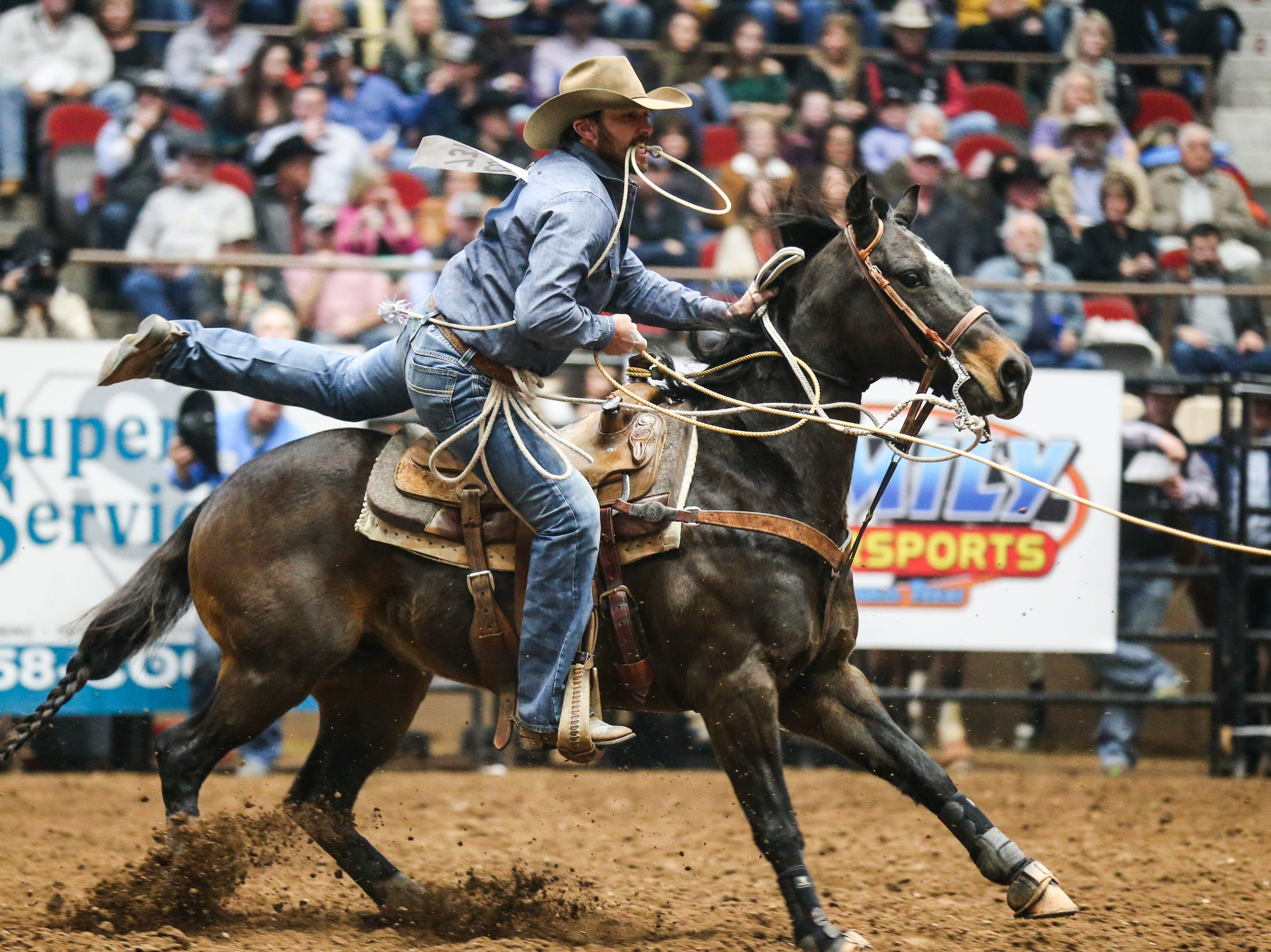 Cade Swor gets off his horse to tie down a calf during the 3rd performance of the San Angelo Stock Show & Rodeo Saturday, Feb. 2, 2019, at Foster Communications Coliseum.