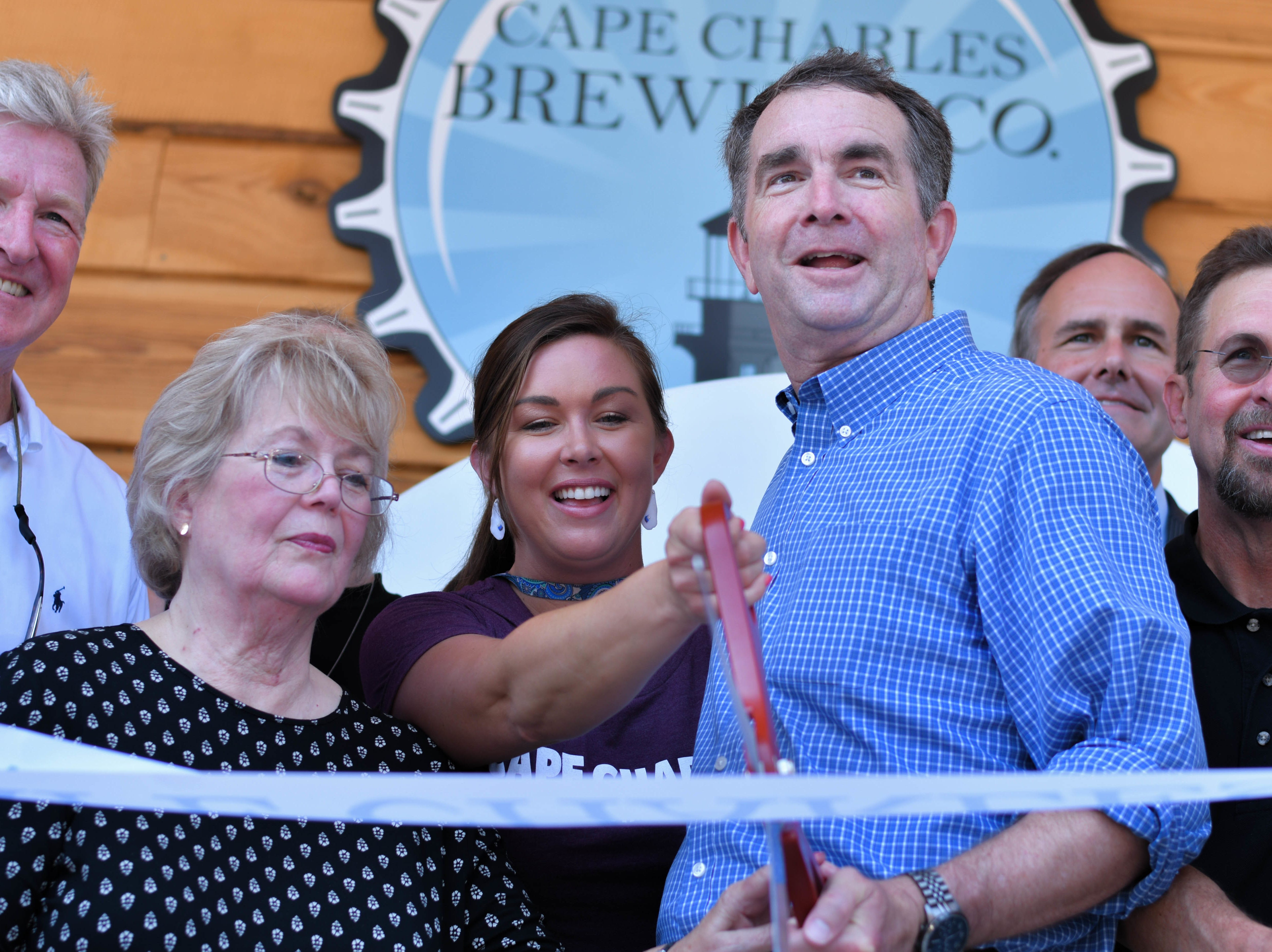 Gov. Ralph Northam poses with Mark, Chris, Deborah Marshall and family in front of the recently opened Cape Charles Brewing Company in Cape Charles on Friday, July 27, 2018.