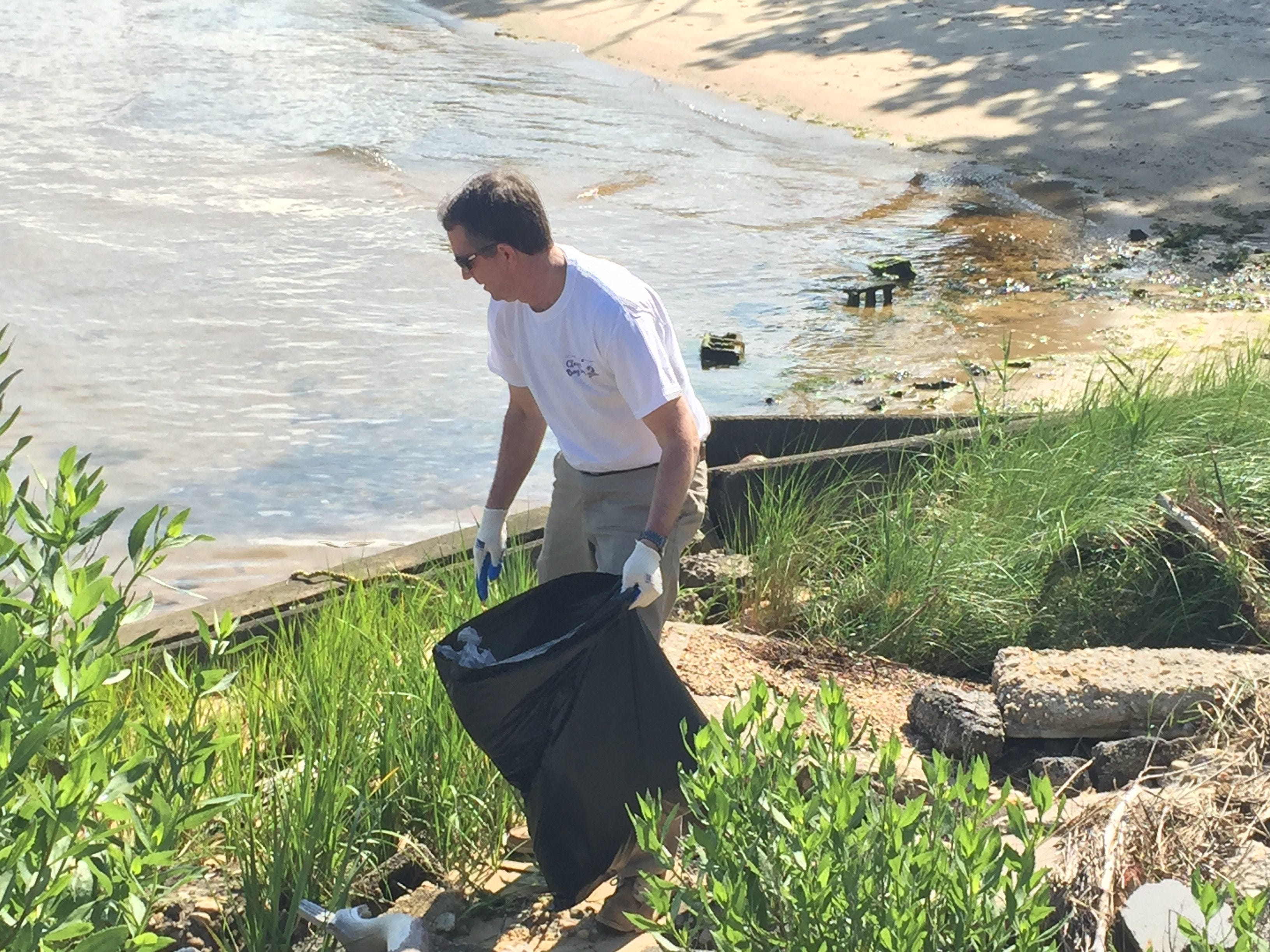 Gov. Ralph Northam picks up trash along Cape Charles Harbor during a Clean the Bay event in Cape Charles on Saturday, June 2, 2018.