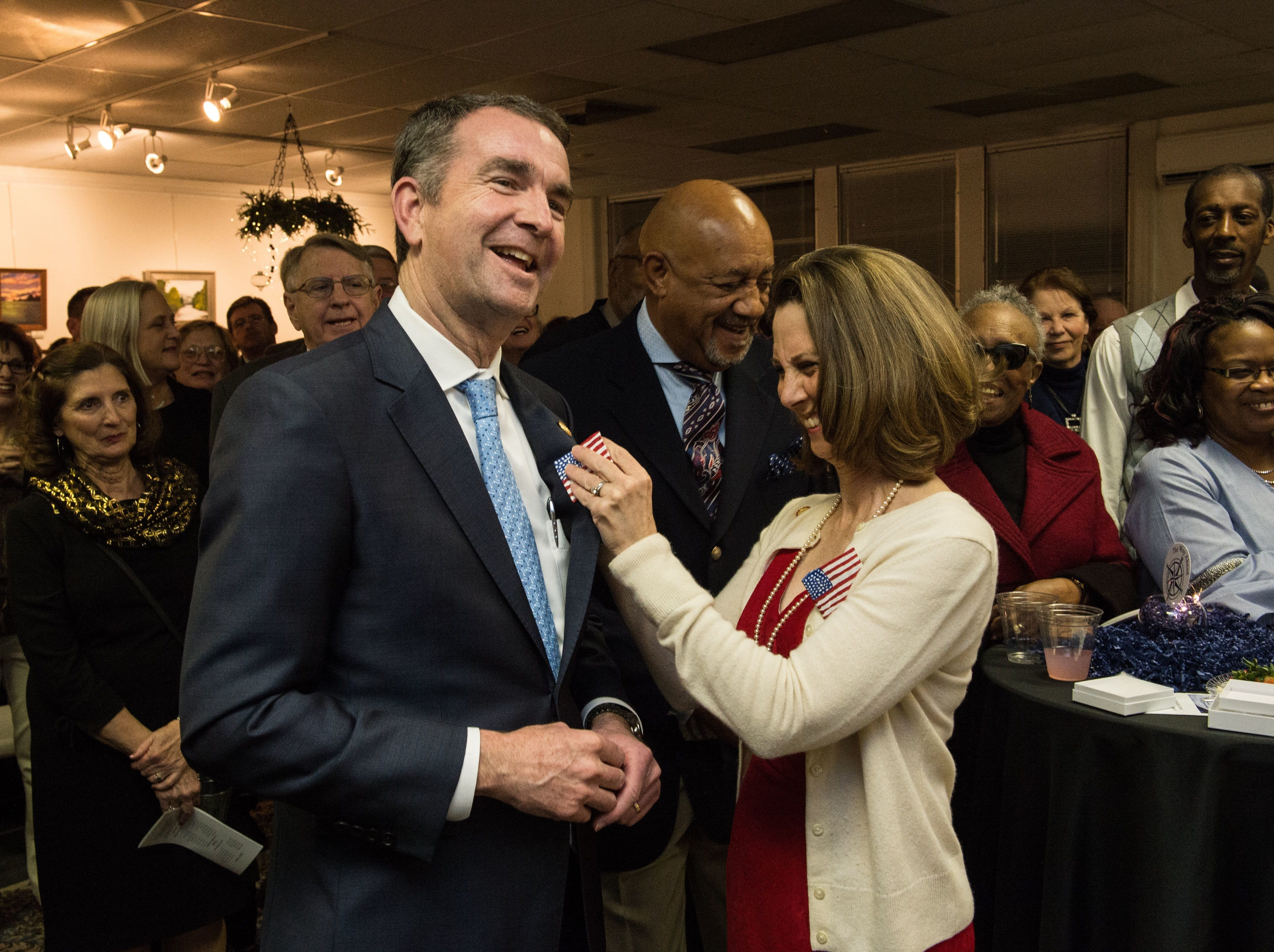 Virginia first lady Pamela Northam pins a paper mache flag on Gov. Ralph Northam during a fundraising gala at the Historic Onancock School on Saturday, Feb. 3, 2018.