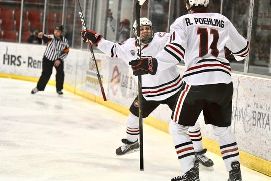 St. Cloud State's Ryan Poehling (#11) and Blake Lizotte (#27) go in for a celebration after taking a 1-0 lead against Miami University in Saturday's NCHC contest at the Herb Brooks National Hockey Center.