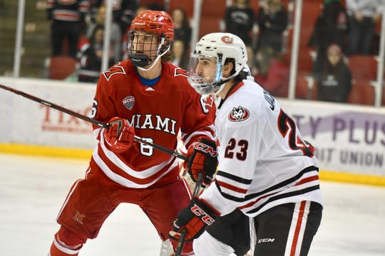 St. Cloud State senior Robby Jackson (#23) fights for a better position against a Miami University defender in Saturday's NCHC contest at the Herb Brooks National Hockey Center.
