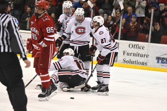 St. Cloud State junior Jack Ahcan (#12) picks himself up off the ice after scoring a goal and giving the Huskies a 2-0 lead in Saturday's NCHC contest against Miami University at the Herb Brooks National Hockey Center.