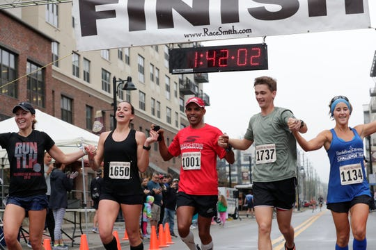 Olympic medalist Meb Keflezighi, center, crosses the finish line while he runs hand in hand with other Tallahassee half marathon runners, Sunday, Feb. 3, 2019.