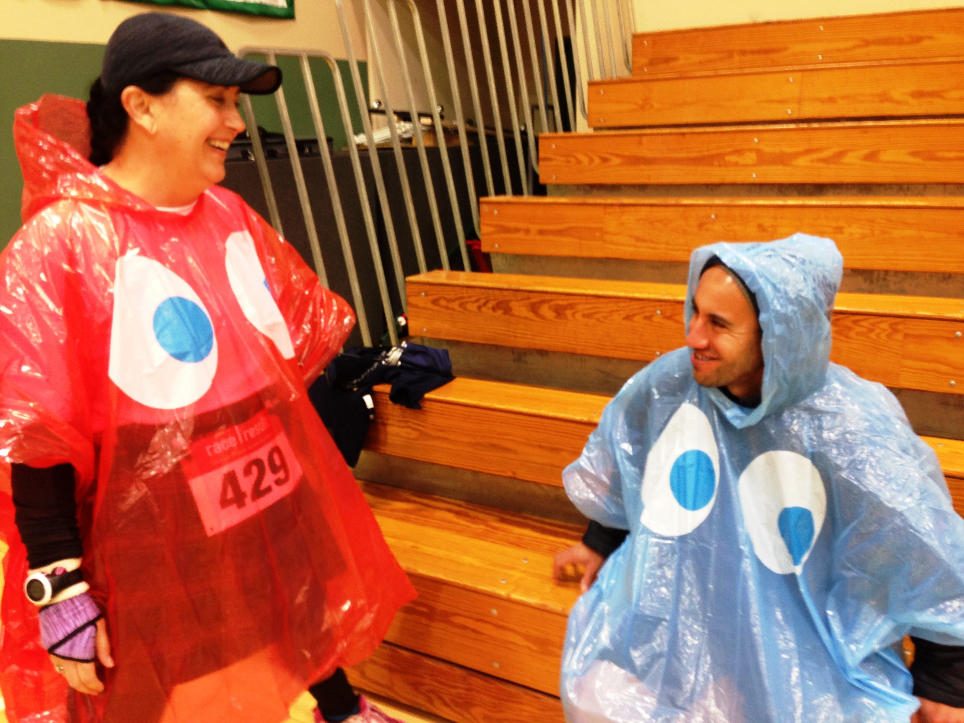 Mary Hodges and Alberto Lopez, of Los Angeles, take a break from the rain inside the gymnasium during the fifth annual Sisters of Notre Dame Nun Run, presented by La Reina High School and Middle School in Thousand Oaks on Saturday.