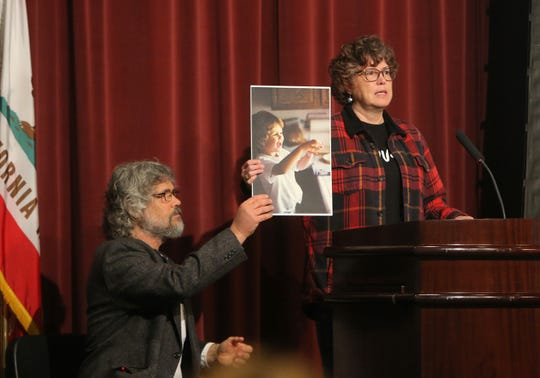 Susan and Marc Orfanos hold up a photo of their son Telemachus Orfanos during a forum on gun violence Sunday at Westlake High School. Telemachus Orfanos was one of the victims of the shooting at the Borderline Bar & Grill.