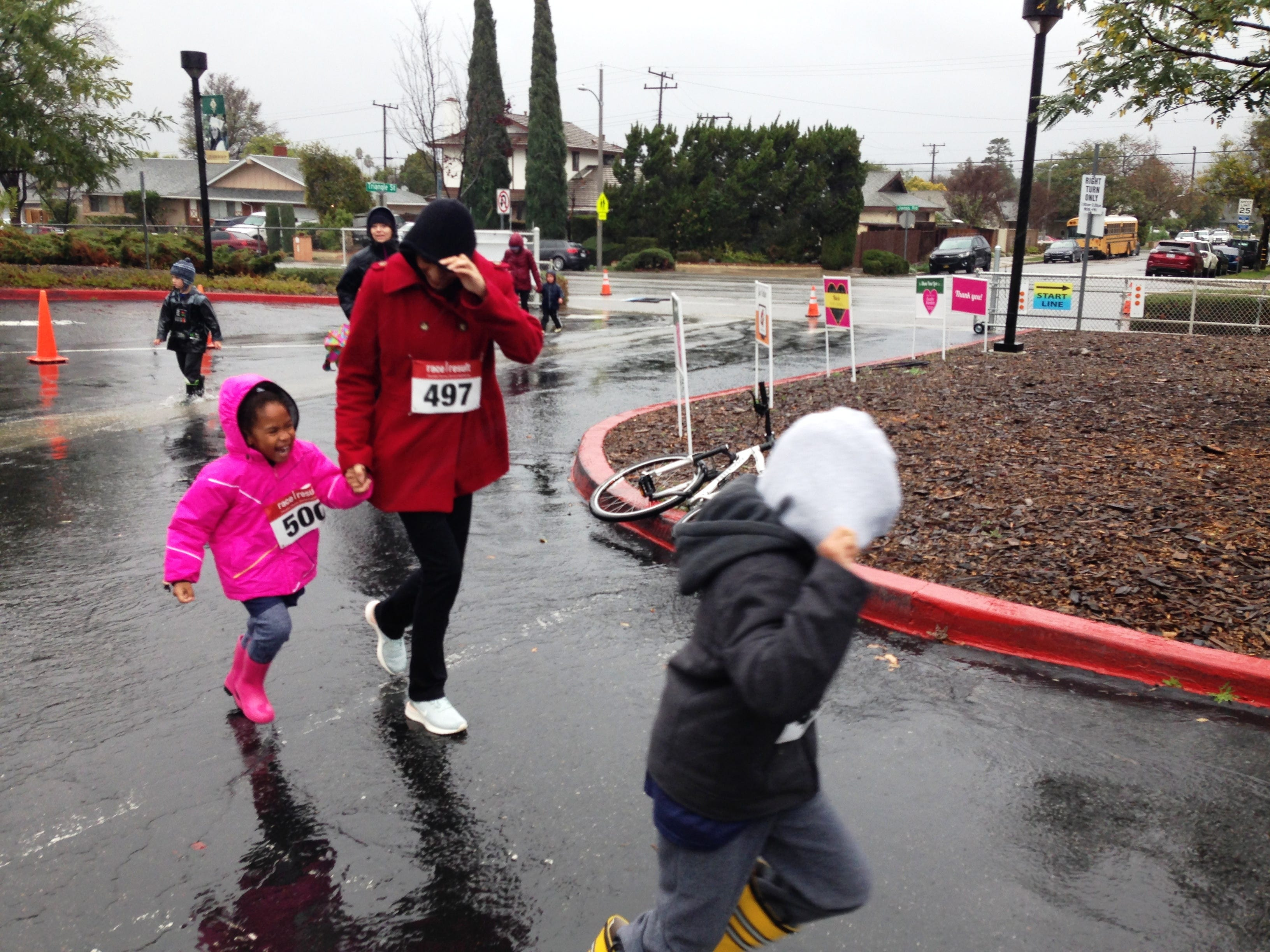 Event participants run through the rain to the finish line during the fifth annual Sisters of Notre Dame Nun Run, presented by La Reina High School and Middle School in Thousand Oaks on Saturday.