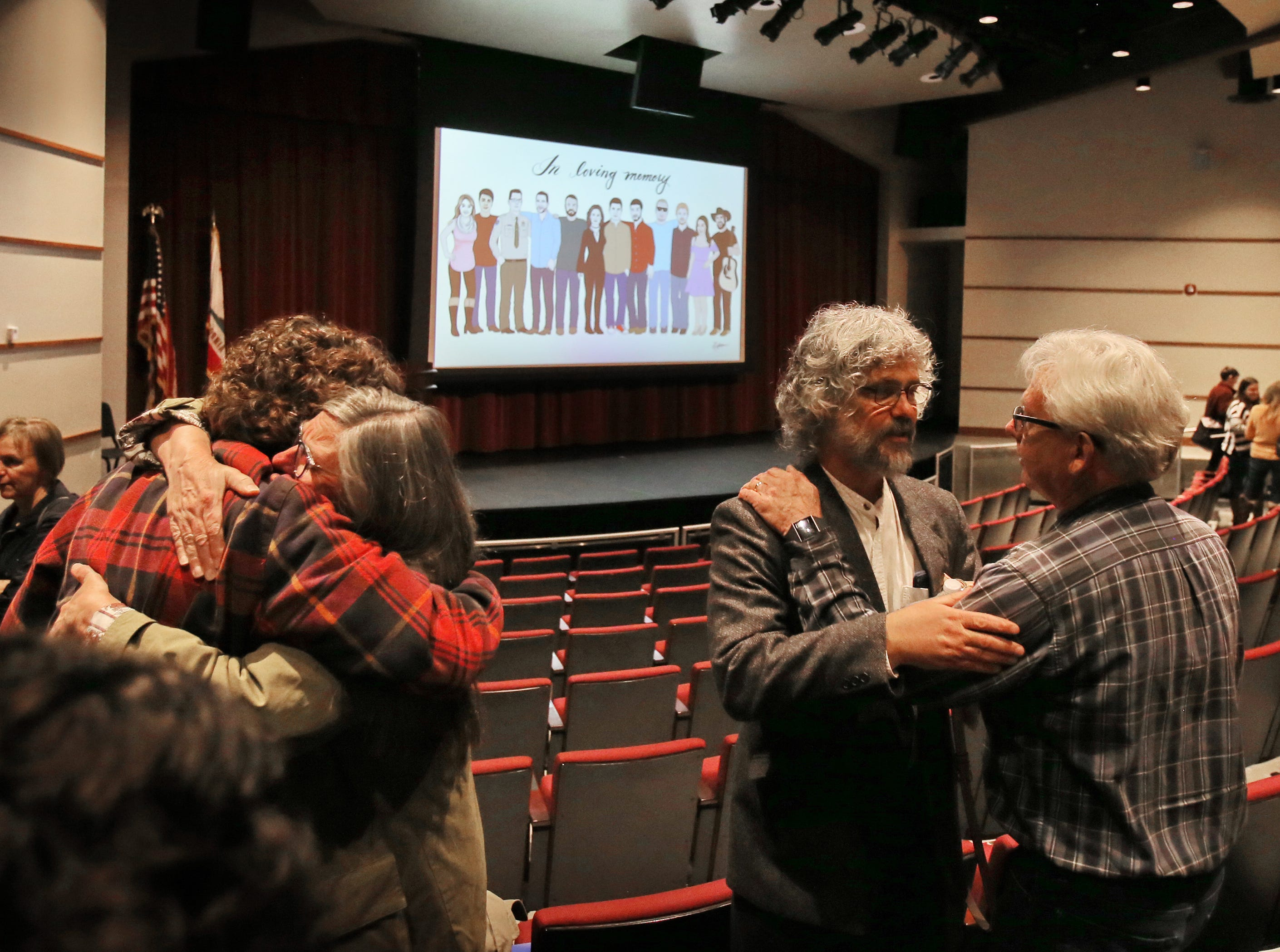 Family friends console Susan Orfanos, left in the red plaid shirt, and her husband Marc, center, after a gun violence forum Sunday at Westlake High School in Thousand Oaks. The Orfanos' son Telemachus Orfanos was among the victims of the shooting at Borderline Bar & Grill. Around 200 people, including local lawmakers, attended the event.