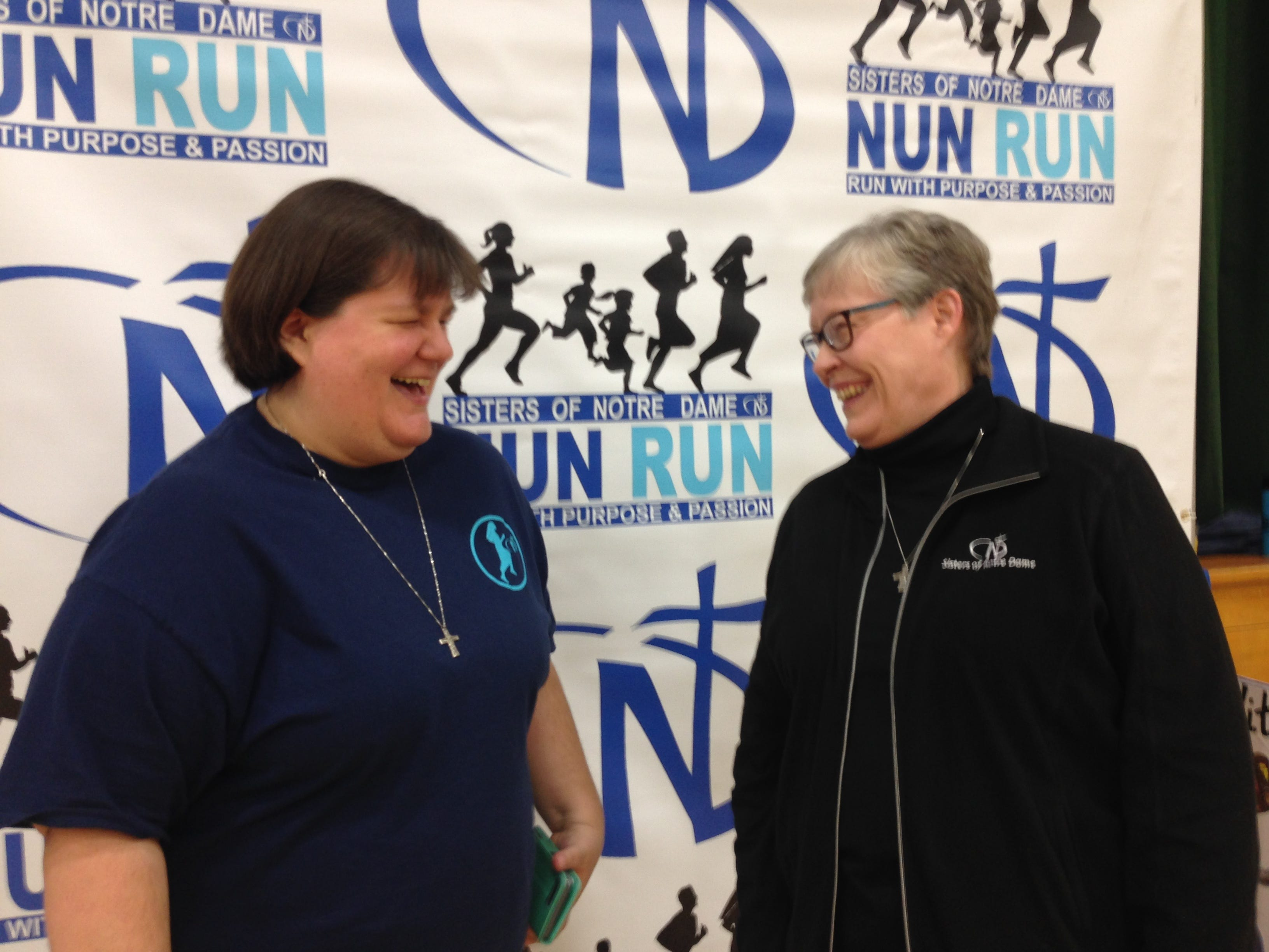 Sister Jenny Zimmerman and Sister Val Roxburgh, of Long Beach, banter with each other during the community service fair inside the school gymnasium during the fifth annual Sisters of Notre Dame Nun Run, presented by La Reina High School and Middle School in Thousand Oaks on Saturday.