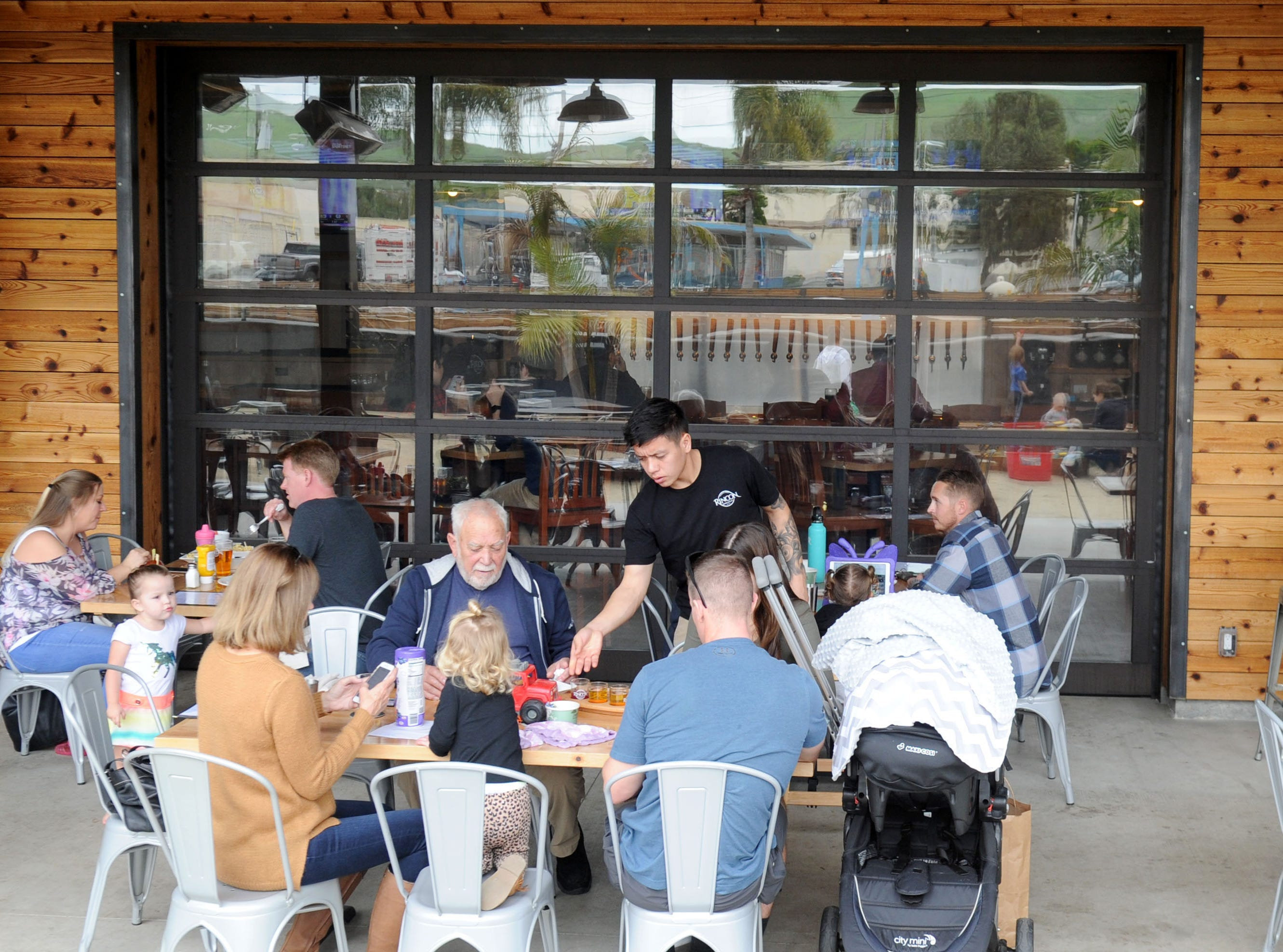 A group of people eat outside in the patio area of the Rincon Brewery in Ventura.