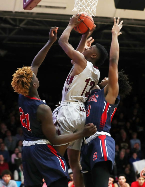 Iona's Ronald Greene Jr. (13) tries to go up for a shot in front of Stepinac's Adrian Griffin Jr. and Malcolm Chimezie during basketball action at Iona College in New Rochelle Feb. 2,  2019.