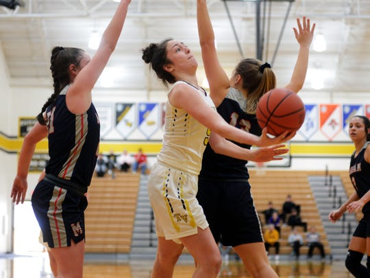 Janie McLoughlin shoots between Kaylie Apperson, left, and Riley Coon during Tri-Valley's 78-53 win against Morgan on Saturday in Dresden.
