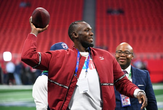 Olympic champion track and field champion Usain Bolt throws a football on the field before Super Bowl LIII at Mercedes-Benz Stadium.