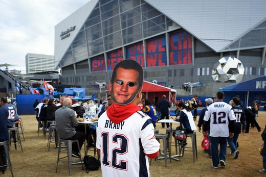 A New England Patriots fan wears a Tom Brady mask before Super Bowl LIII.