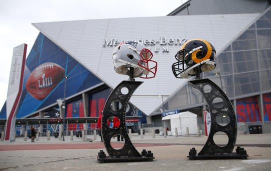 Helmets for the New England Patriots and Los Angeles Rams on display outside before Super Bowl LIII at Mercedes-Benz Stadium.