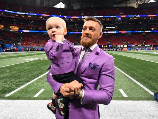 UFC fighter Conor McGregor holds his son Conor Jack McGregor Jr. on the sidelines of Merdeces-Benz Stadium before Super Bowl LIII between the New England Patriots and the Los Angeles Rams.