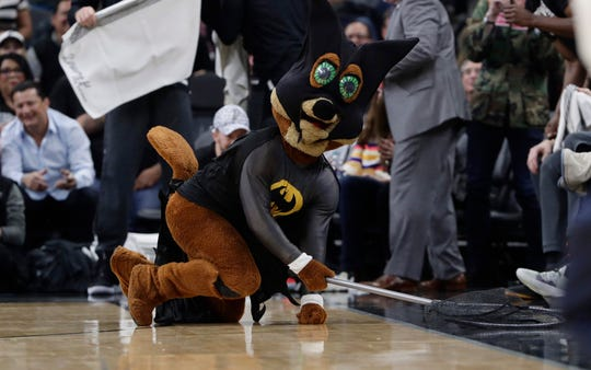 San Antonio Spurs mascot, The Coyote, uses a net as he dives for and catches a bat during Saturday's home game.