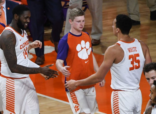 Clemson guard Lyles Davis (3), middle, and Clemson forward Elijah Thomas (14), left, greet Clemson forward Javan White (35), right, coming in during a break in the first half at Littlejohn Coliseum in Clemson Wednesday, January 16, 2019.