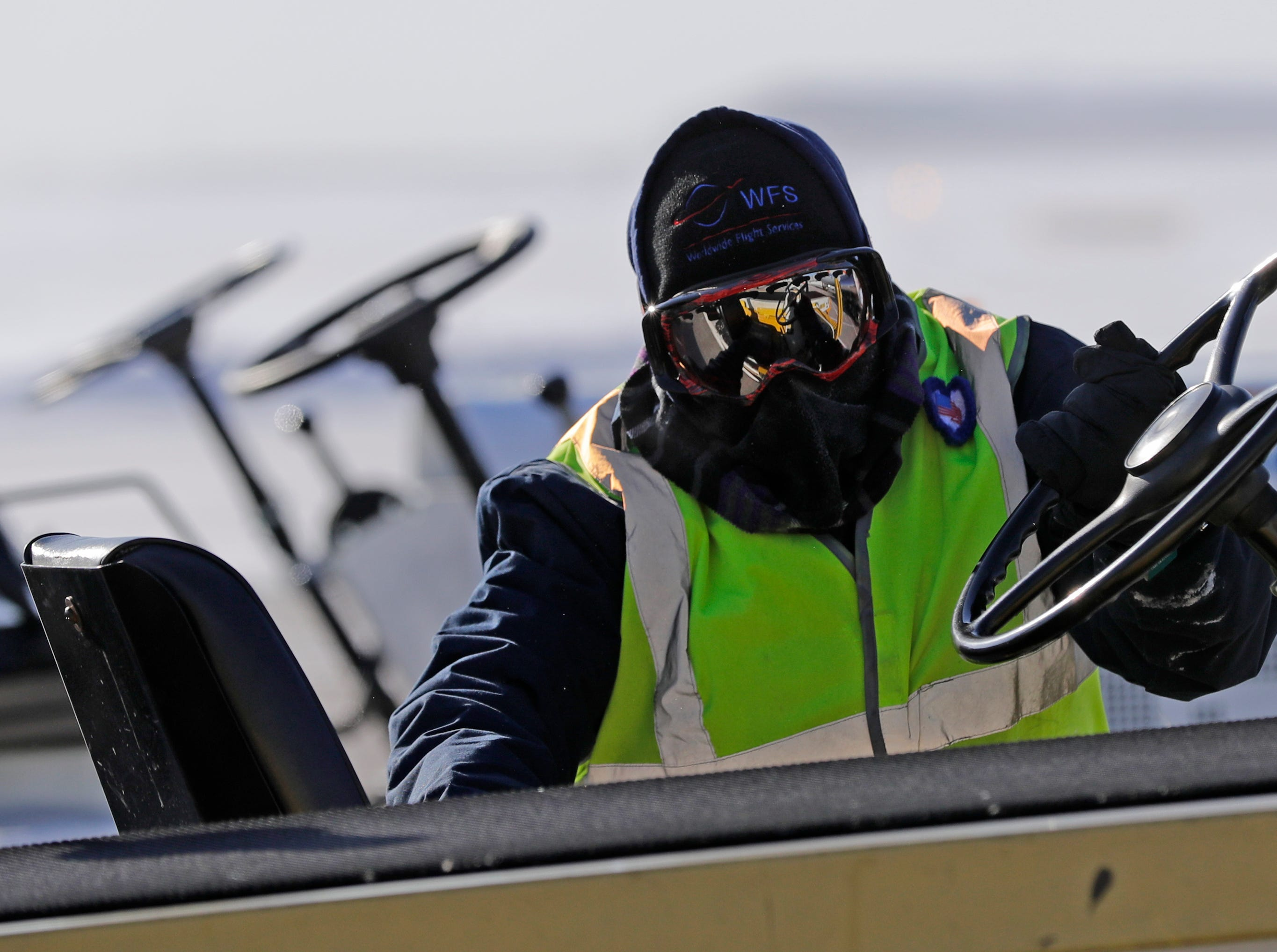 A Worldwide Flight Services employee braves frigid temperatures and high winds to use a luggage vehicle to remove luggage from an arriving Allegiant Airlines jet Wednesday, January 30, 2019, at the Appleton International Airport in Greenville, Wis. 