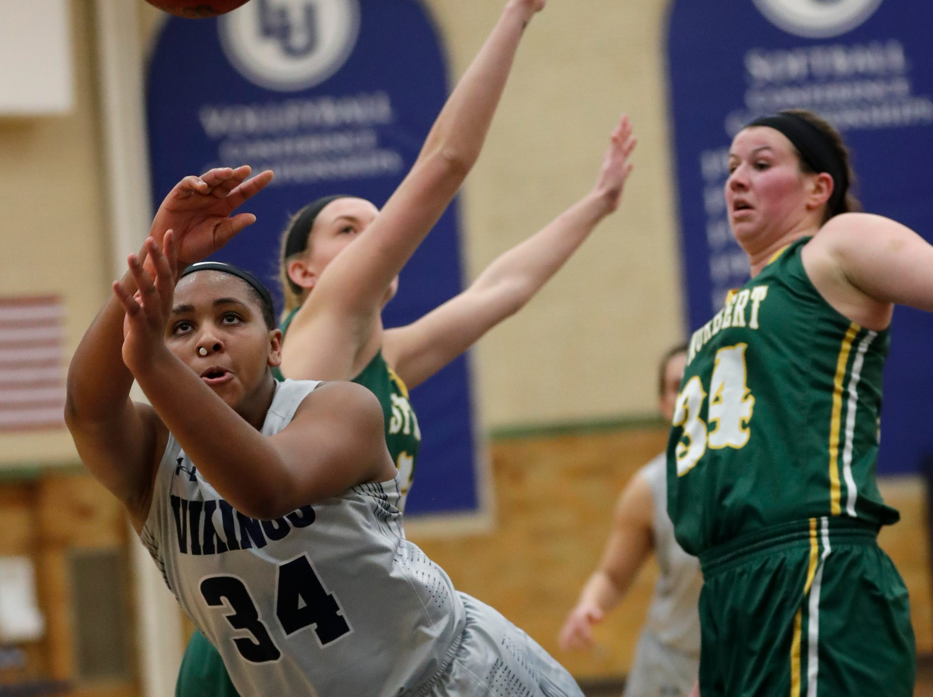 Lawrence University's Kenya Earl, center, drives to the basket against St. Norbert College's Jessica Boerner, left, and Hannah Ciesielczyk, right, during their women's basketball game Thursday, January 31, 2019, at Alexander Gymnasium in Appleton, Wis. A foul was called on Ciesielczyk on the play.
