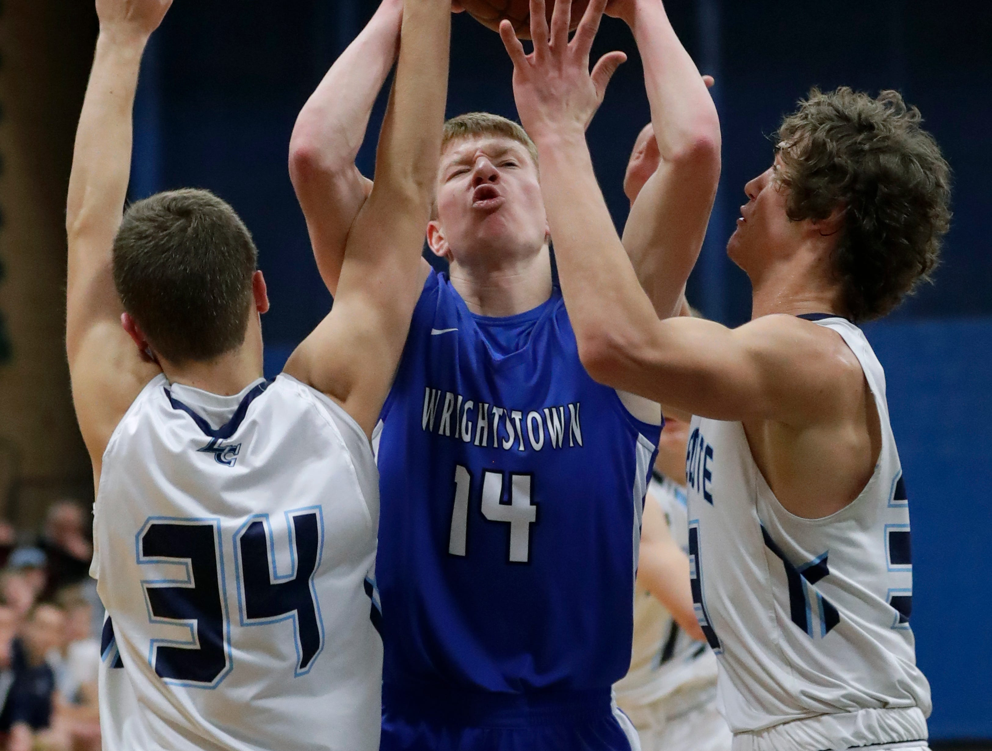 Little Chute High School's Connor Christopherson, left, and Isiah Boe, right, defend against Wrightstown High School's Mayson Hazaert during their boys basketball game Friday, February 1, 2019, in Little Chute, Wis. 