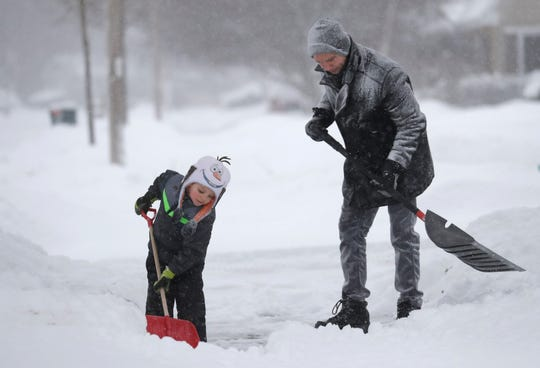 David Liebhard gets help from his 4-year-old son Levi as the two shovel their driveway during a snowstorm in Appleton