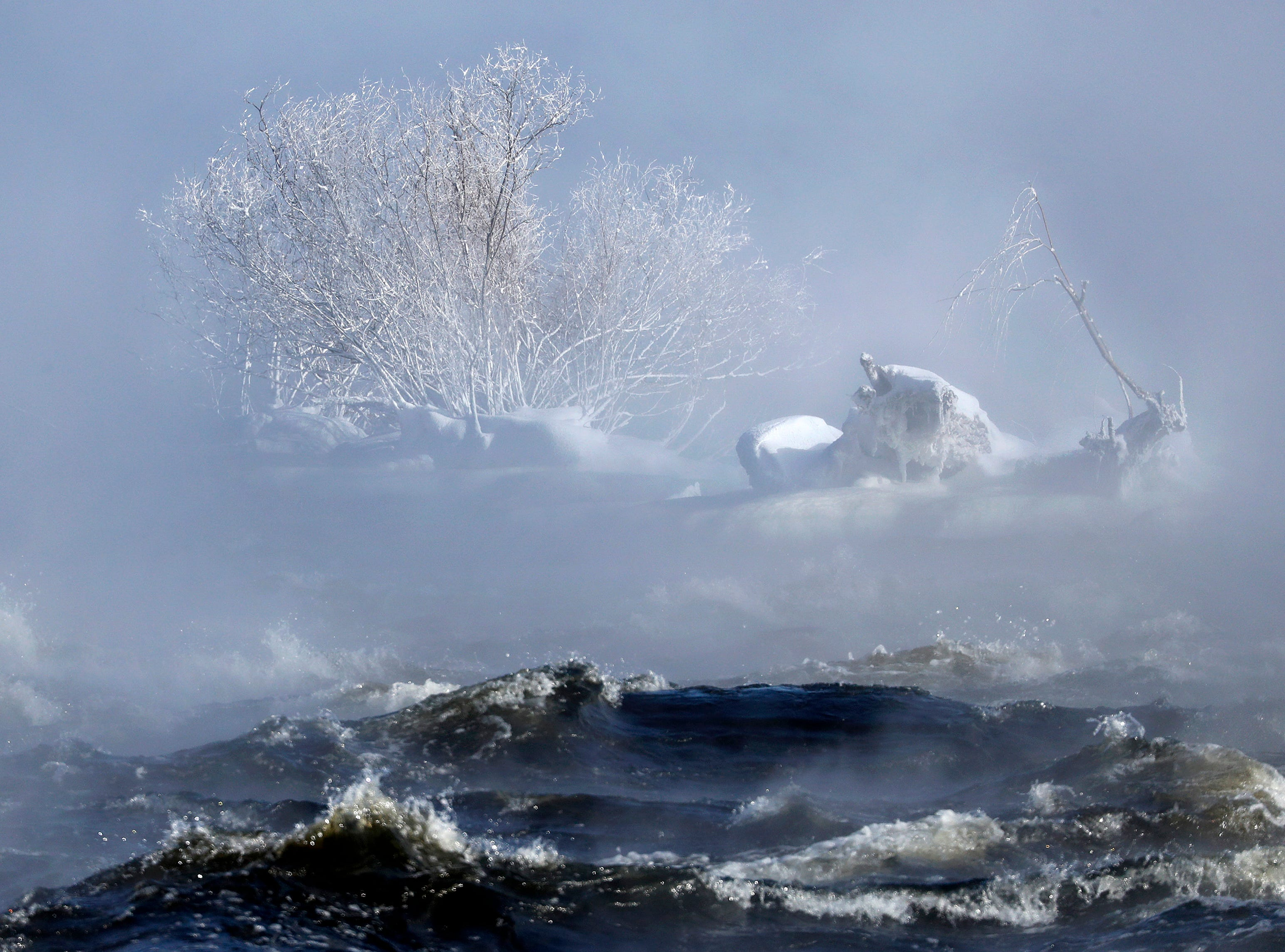 Steam and water from the Fox River whip around a small outcropping of trees and stone Wednesday, Jan. 30, 2019, in Appleton, Wis.