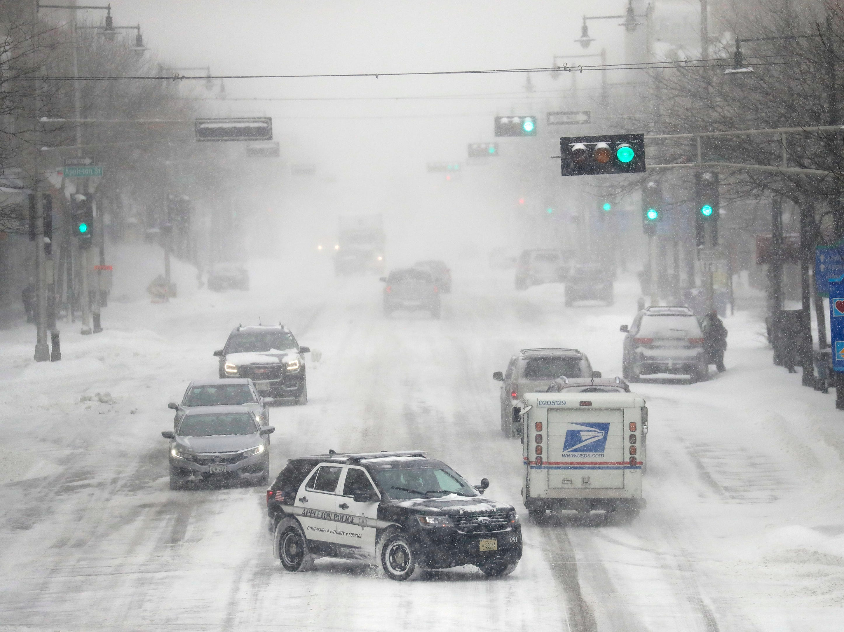 Traffic moves slowly along College Avenue during a snowstorm Monday, January 28, 2019, in downtown Appleton, Wis. 