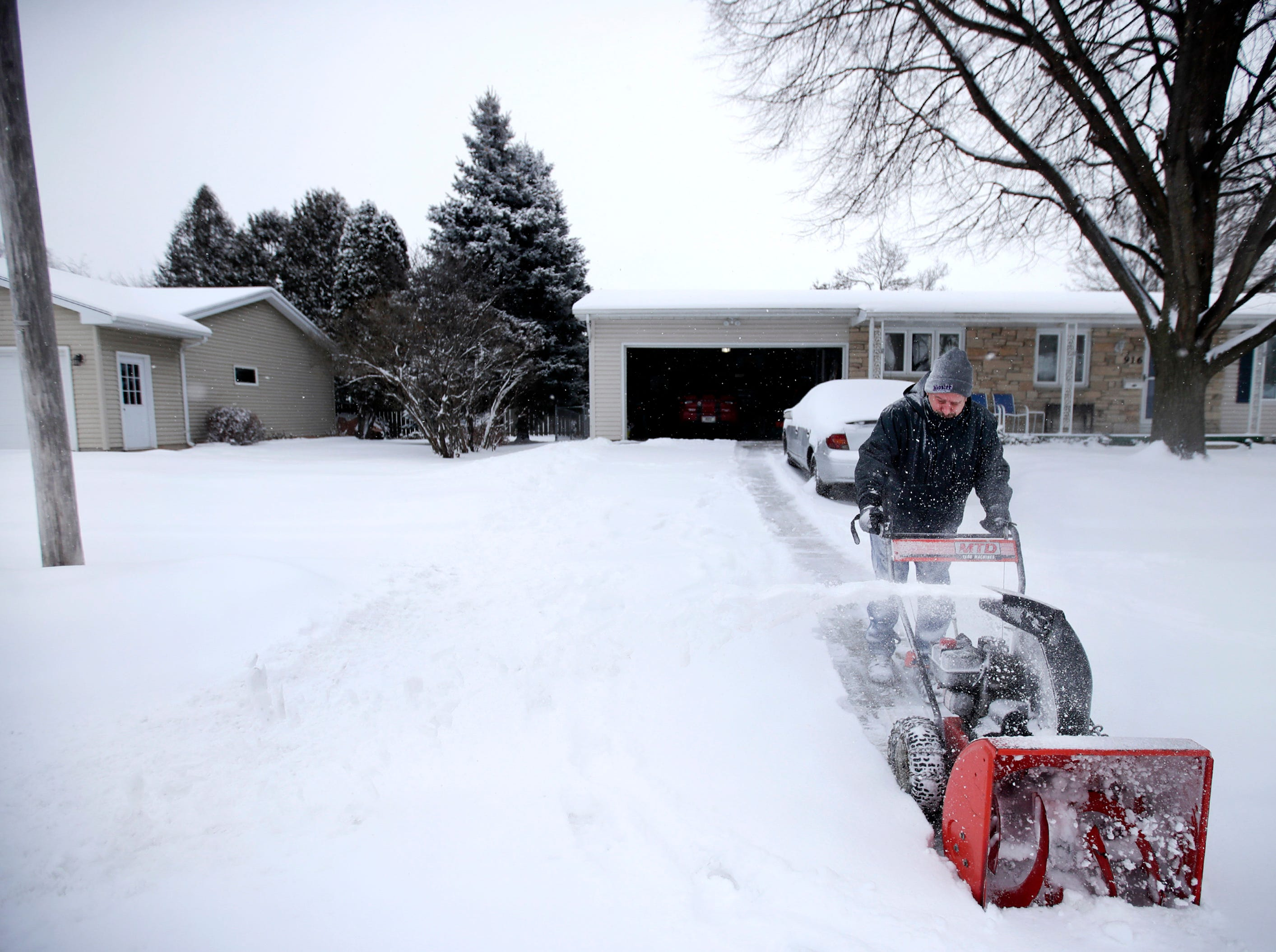 Daniel Putzer, of Oshkosh, snowblows his driveway Wednesday, Jan. 23, 2019, in Oshkosh, Wis.