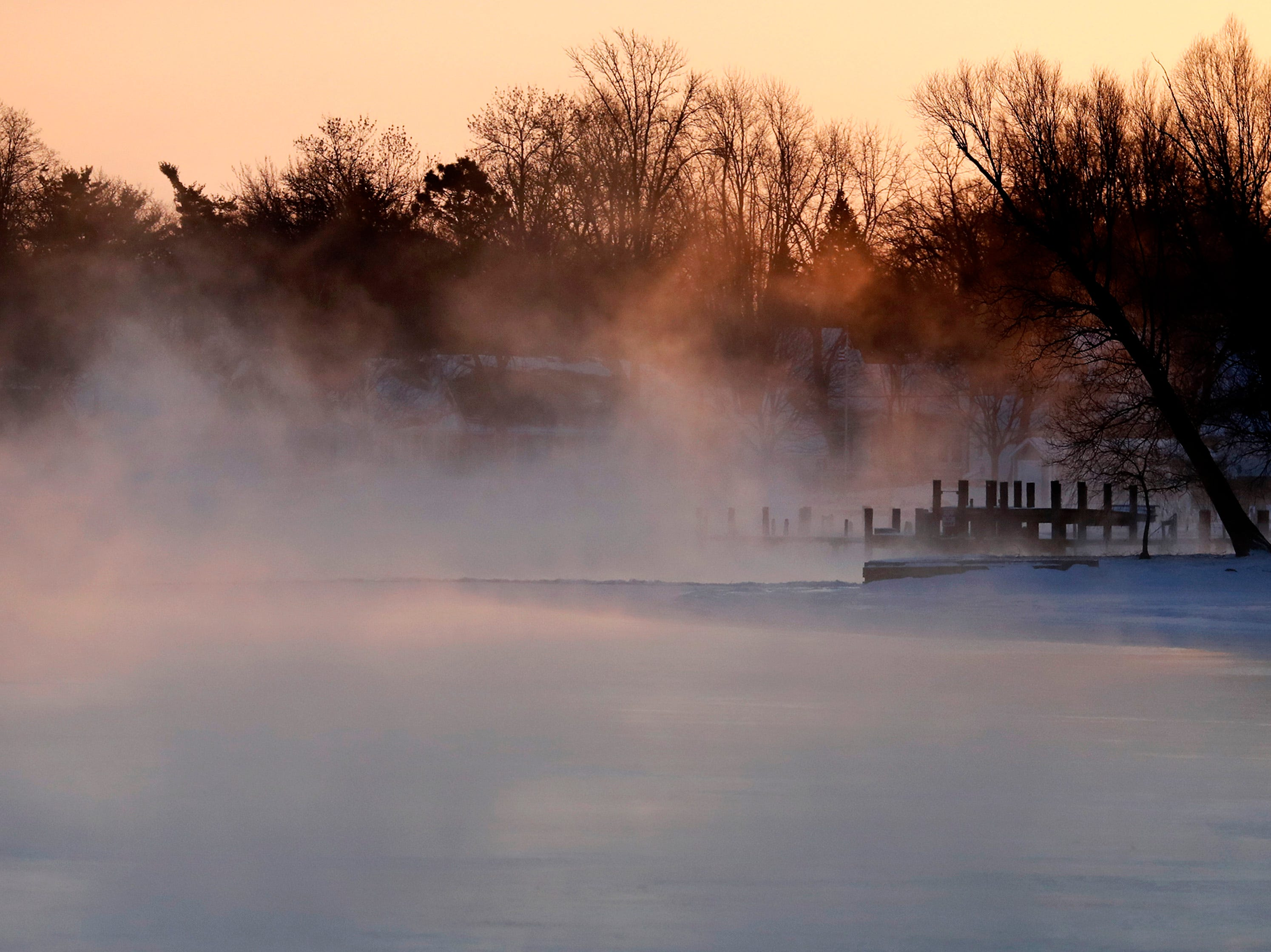 Light from the sunrise illuminates steam coming from the Menasha Channel as wind chills ranged from 20 to 40 below in the Fox Cities Wednesday, Jan. 30, 2019, in Menasha, Wis.